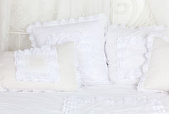 Beautiful and soft white laced pillows on bed. stock images