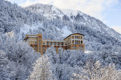Beautiful Solis Sochi Hotel surrounded with snowy forest trees on a sunny mountain slope background scenic landscape Royalty Free Stock Image