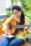 Beautiful songwriter writing on note paper with acoustic guitar. Pretty songwriter smiling and having fun enjoy hobby concept. Asian woman writing on note paper royalty free stock photos