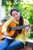 Beautiful songwriter writing on note paper with acoustic guitar. Pretty songwriter tooth smiling and having fun enjoy hobby concept. Asian woman writing on note royalty free stock photos