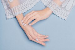 Beautiful hands with blue nails on a blue background royalty free stock photo