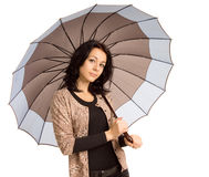 Beautiful sophisticated woman. Sheltering under a beige and white umbrella which matches her stylish outfit isolated on white Royalty Free Stock Images
