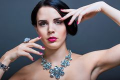 Beautiful sophisticated woman. Beautiful sophisticated dark haired woman wearing elegant showy gemstone jewellery posing with bare shoulders and her hand raised Royalty Free Stock Photos