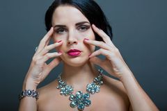Beautiful sophisticated woman. Beautiful sophisticated dark haired woman wearing elegant showy gemstone jewellery posing with bare shoulders and her hand raised Stock Image