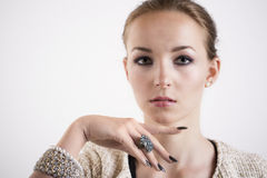 Beautiful sophisticated young woman. Wearing modern jewellery and nail varnish posing with her finger under her chin looking at the camera with a serious Royalty Free Stock Image