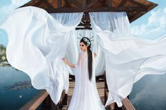 A beautiful sorceress stands on the background of a wooden gazebo by the water, with a white air dress. In the picture royalty free stock photo
