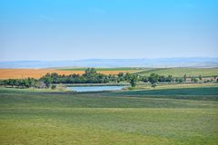 Beautiful Landscape with green grass, yellow sand and blue sky. Beautiful South Dakota Landscape with green grass, hilly yellow sand and big blue sky royalty free stock photography
