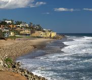 Beautiful Southern California Beach with Mansions. A beautiful day at the rocky california beach, County Line Beach.  The rocky shore line in the foreground and Royalty Free Stock Images