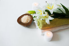 Beautiful spa composition with lily flowers, towels, soap, bath salt and candles Stock Photo