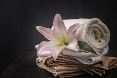 Beautiful spa composition with towels and lily flower. On dark background royalty free stock images
