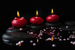 Beautiful spa concept of candles, zen stones with drops Royalty Free Stock Photos
