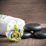 Beautiful spa concept of passiflora flower, black zen stones and. White towels on wooden background, closeup stock images