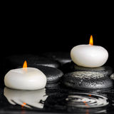 Beautiful spa concept of white candles and black zen stones  Stock Photo