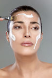 Beautiful Spa Girl. Skincare concept. Beautiful spa woman applying a spa treatment with cream on her face. Perfect skin. Skincare concept. Nude makeup Royalty Free Stock Photos