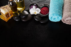 Beautiful Spa Set Spa Products with Essential Oils, Soap, Towel, Spa Sea Salt on Dark Wet Background. Horizontal with Copy Space. Stock Images