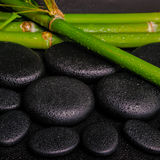 Beautiful spa setting of zen basalt stones and natural bamboo st. Ems with dew, closeup stock photography