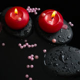 Beautiful spa still life of candles, zen stones with drops Stock Photos
