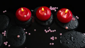 Beautiful spa still life of candles, zen stones with drops Royalty Free Stock Photo
