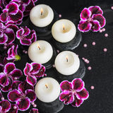 Beautiful spa still life of geranium flower, beads and candles i Royalty Free Stock Photo