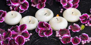 Beautiful spa still life of geranium flower and candles in rippl Stock Images