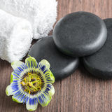 Beautiful spa still life of passiflora flower, black zen stones. And white towels on wooden background, closeup royalty free stock images