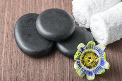 Beautiful spa still life of passiflora flower, black zen stones. And white towels on wooden background, closeup royalty free stock photography