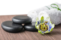 Beautiful spa still life of passiflora flower, black zen stones. And white towels on wooden background is isolated, closeup royalty free stock photography