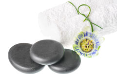 Beautiful spa still life of passiflora flower, black zen stones. And white towels on wooden background is isolated, closeup royalty free stock images
