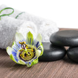 Beautiful spa still life of passiflora flower, black zen stones. And white towels on wooden background is isolated, closeup stock photos