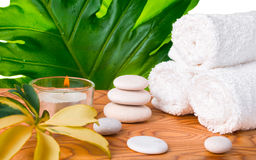 Beautiful spa still life with white stones, candle, towels, big Stock Photos