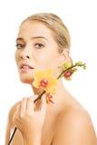 Beautiful spa vrouw met oranje orchidee Stock Foto