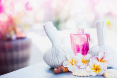 Beautiful spa or wellness treatment and product with compress balls, lotion, frangipani flower at spring or summer nature backgro Stock Image