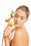 Beautiful spa woman with orange orchid Stock Images