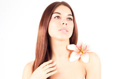 Beautiful spa woman touching her face. Woman with pink flower. Woman with fresh and clear skin. SPA woman touching her face. Woman with pink flower. Woman with Stock Images