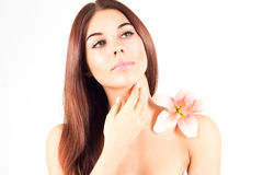 Beautiful spa woman touching her face. Woman with pink flower. Woman with fresh and clear skin. Woman touching her face. Woman with pink flower. Woman with Stock Images