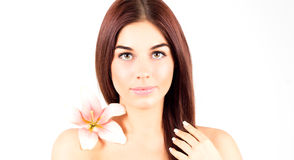 Beautiful spa woman touching her hair. Woman with pink flower smiling. Woman with fresh and clear skin. Stock Photo