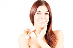 Beautiful spa woman touching her neck. Woman with pink flower smiling with white teeth. Woman with fresh and clear skin. Royalty Free Stock Image