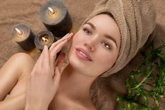 Free Beautiful Spa Woman With A Towel On Her Head Lying And Touching Face Skin. Skincare. Beauty Smiling Model Girl In Spa Salon Stock Image - 162196311