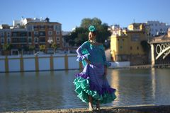 The beautiful Spanish woman with the flamenco dress near the river Guadalquivir in Seville, in the famous neighborhood of Triana. Beauties and wonders of ancient stock image