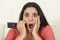 Beautiful Spanish woman home watching television on couch at  living room surprised and excited Stock Images