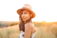 Beautiful spanish young woman close up portrait. Wearing a fashion stylish hat looking at camera outdoors over sunrise background Stock Photography