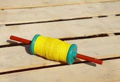 A beautiful spindles with yellow thread to fly kites Royalty Free Stock Image