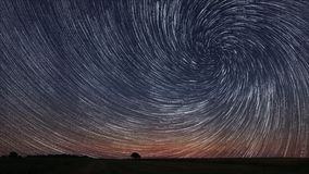 Free Beautiful Spiral Star Trails Over Filed With Lonely Tree. Stock Photography - 58573732