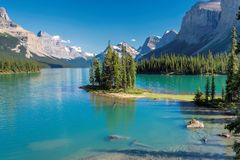Beautiful Spirit Island in Maligne Lake, Jasper National Park, Alberta, Canada. Beautiful turquoise waters of the Maligne Lake with snow-covered peaks above it Royalty Free Stock Photos