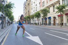 Beautiful sport african woman running in the street, health lifestyle c Royalty Free Stock Photos
