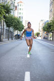 Beautiful sport african woman running in the street, health lifestyle c Royalty Free Stock Image