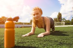Young sportive girl with curly hairstyle on stadium. Beautiful Sport on Fotball Stadium. Sportive Lady is Doing Sports and Looking at the Camera. Inrensive Push royalty free stock images