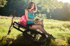 Beautiful sport girl with bicycle read a map. Beautiful sport girl with bicycle and backpack read a map Stock Photo