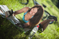 Beautiful sport girl lay on a grass and read a map. Beautifu smilingl sport girl lay on a grass near the bicycle and read a map Royalty Free Stock Photo