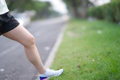 beautiful sport girl legs stand on wayside grass in morning before run with running shoe royalty free stock images